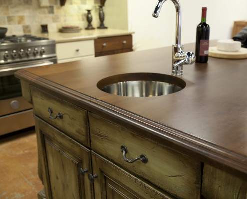 Distressed kitchen cabinets wooden countertop with modern stainless steel faucet and sink.